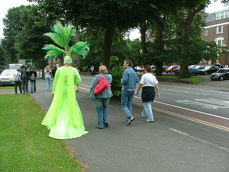 man in green outfit walking with people