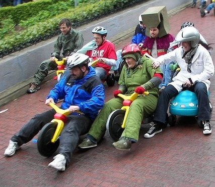 guys racing tricycles
