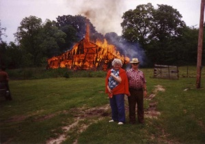 couple standing in front of burning barn